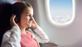 Adorable young girl traveling by an airplane. Child sitting by aircraft window and looking outside while listening to music. royalty free stock photo