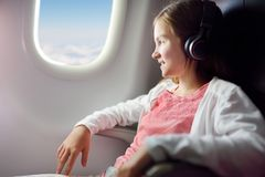Adorable young girl traveling by an airplane. Child sitting by aircraft window and looking outside while listening to music. stock photo