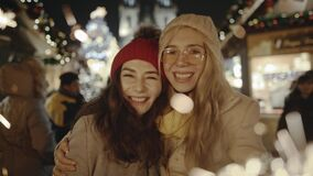 Adorable young girlfriends laughing and hugging at festive cozy fair in the central square of Prague. Gorgeous women