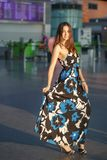 Adorable young lady. Posing at the airport dressed in a long dress royalty free stock photo
