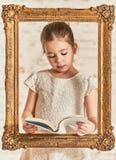 Adorable young little girl reading a book Stock Photo