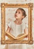 Adorable young little girl reading a book Stock Photos