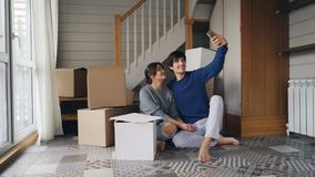 Adorable young people girl and guy are taking selfie expressing love and tenderness kissing and hugging sitting on floor stock footage