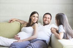 Adorable young pregnant family in living room Royalty Free Stock Photo