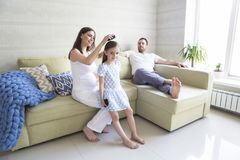 Adorable young pregnant family in living room. Happiness and love concept. Adorable young pregnant family in living room. Mother combing her daughter`s hair royalty free stock images
