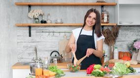Adorable young vegan woman mixing fresh appetizing salad in bowl posing in kitchen at home