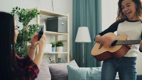 Adorable young woman amateur guitarist is playing the guitar and singing while her Asian friend is recording video for. Adorable young woman amateur guitarist is stock video footage