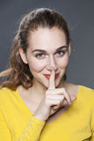 Adorable young woman asking to keep quiet for discretion Royalty Free Stock Image