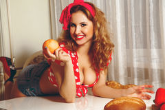 Adorable young woman with curly hair in pinup style posing on ta. Ble and smiling on camera. Pin-up woman. Pin up style woman in the kitchen. Pin up clothes Stock Photo