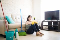 Happy woman sitting after cleaning house. Adorable young woman feeling blessed after completing house chores sitting in living room with rest of couch Stock Image
