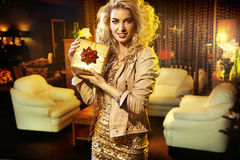 Adorable young woman holding a gift royalty free stock images