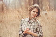 Adorable young woman in plaid shirt on cozy country walk on field Stock Images