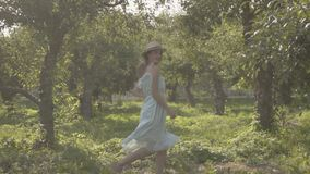 Adorable young woman in straw hat and long white dress running through the green summer garden. Carefree rural life. Attractive young woman in straw hat and long stock video