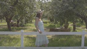 Adorable young woman in straw hat and long white dress standing in the green summer garden behind the fence. Rural. Cute young woman in straw hat and long white stock video footage