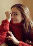 Adorable young woman in sweater at home smiling Stock Photography
