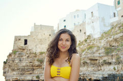 Adorable young woman wearing a bikini yellow enjoying her holiday on Adriatic rocky coast background. Travel in Europe. stock photography