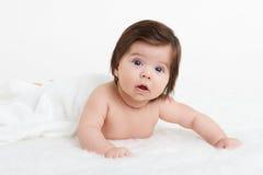 Adorablemente mentira del bebé en la toalla blanca en cama Concepto feliz de la niñez y de la atención sanitaria Foto de archivo libre de regalías