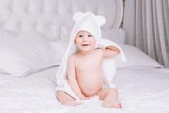 Adorablemente mentira del bebé en la toalla blanca en cama Concepto feliz de la niñez y de la atención sanitaria Imagenes de archivo