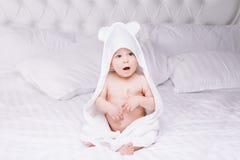 Adorablemente mentira del bebé en la toalla blanca en cama Concepto feliz de la niñez y de la atención sanitaria Fotos de archivo libres de regalías