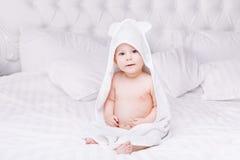 Adorablemente mentira del bebé en la toalla blanca en cama Concepto feliz de la niñez y de la atención sanitaria Fotografía de archivo