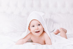 Adorablemente mentira del bebé en la toalla blanca en cama Concepto feliz de la niñez y de la atención sanitaria Imagen de archivo libre de regalías