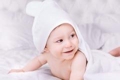 Adorablemente mentira del bebé en la toalla blanca en cama Concepto feliz de la niñez y de la atención sanitaria Imágenes de archivo libres de regalías