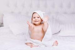 Adorablemente mentira del bebé en la toalla blanca en cama Concepto feliz de la niñez y de la atención sanitaria Foto de archivo