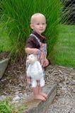 adorableToddler男孩站立与一只被充塞的羊羔在一个绿色庭院里 免版税图库摄影