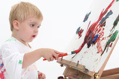 adorabletoddler boy easel painting 免版税图库摄影