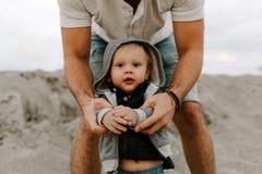 Adorably идеальная молодая семья сына малыша отца и младенца имея время потехи на песчаном пляже во время снаружи захода солнца о стоковые фотографии rf