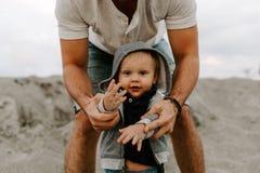 Adorably идеальная молодая семья сына малыша отца и младенца имея время потехи на песчаном пляже во время снаружи захода солнца о стоковые фото