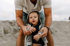 Adorably идеальная молодая семья сына малыша отца и младенца имея время потехи на песчаном пляже во время снаружи захода солнца о стоковые изображения