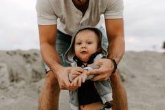 Adorably идеальная молодая семья сына малыша отца и младенца имея время потехи на песчаном пляже во время снаружи захода солнца о стоковое изображение
