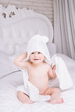 Adorably baby lie on white towel in bed. Happy childhood and healthcare concept. Royalty Free Stock Image