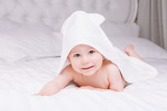 Adorably baby lie on white towel in bed. Happy childhood and healthcare concept. Royalty Free Stock Photos