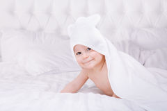 Adorably baby lie on white towel in bed. Happy childhood and healthcare concept. Royalty Free Stock Photography