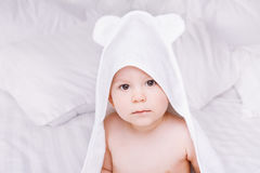 Adorably baby lie on white towel in bed. Happy childhood and healthcare concept. Stock Images