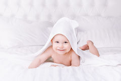 Adorably baby lie on white towel in bed. Happy childhood and healthcare concept. Adorable newborn baby boy with brown eyes sitting wrapped in a white towel with Royalty Free Stock Images