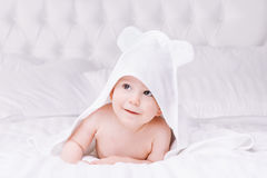 Adorably baby lie on white towel in bed. Happy childhood and healthcare concept. Stock Photography