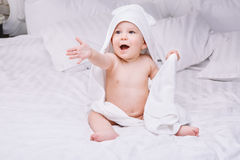 Adorably baby lie on white towel in bed. Happy childhood and healthcare concept. Stock Photo