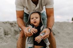 Adorably Perfect Young Father and Baby Toddler Son Family Having Fun Time at the Sandy Beach During Sunset Outside By the Ocean Wa. Ter on Travel Vacation stock images