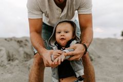 Adorably Perfect Young Father and Baby Toddler Son Family Having Fun Time at the Sandy Beach During Sunset Outside By the Ocean Wa stock image