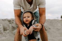 Adorably perfekt ung fader och att behandla som ett barn litet barnsonfamiljen som har roliga Tid på Sandy Beach During Sunset Ou royaltyfri bild