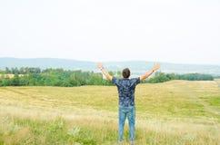 Adoración de moda del adolescente en naturaleza con las manos aumentadas al cielo Foto de archivo