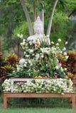 Adoración del budismo con las flores y la guirnalda de ofrecimiento a la estatua de Buda Fotos de archivo libres de regalías