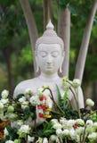 Adoración del budismo con las flores y la guirnalda de ofrecimiento a la estatua de Buda Imagenes de archivo