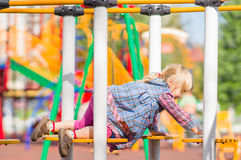 Adorbale girl in dress crawling on playground Royalty Free Stock Photos