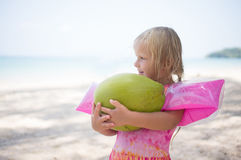 Adorbale girl in swimming suit hold huge green coconut at ocean Stock Images