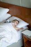 Adorbale litet barn som sovar i hotellrum Arkivbilder
