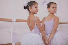 Two little ballerinas talking after dancing lesson royalty free stock images